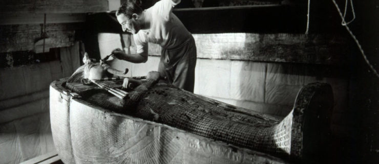 Howard Carter brushing dust off King Tut's mummy.