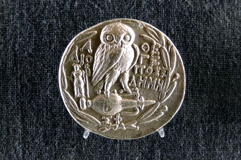 Owl of Athena imprinted on silver coin.