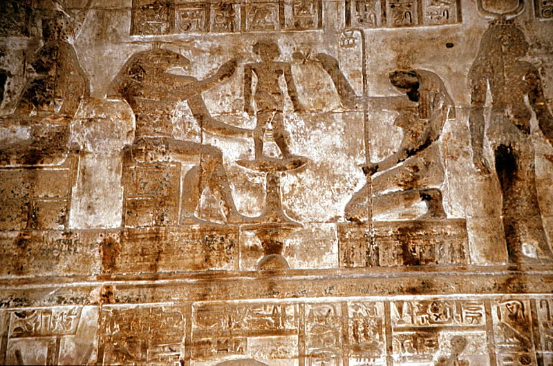 The god Khnum, accompanied by Heqet, moulds Ihy in a relief from the mammisi (birth temple) at Dendera Temple complex.
