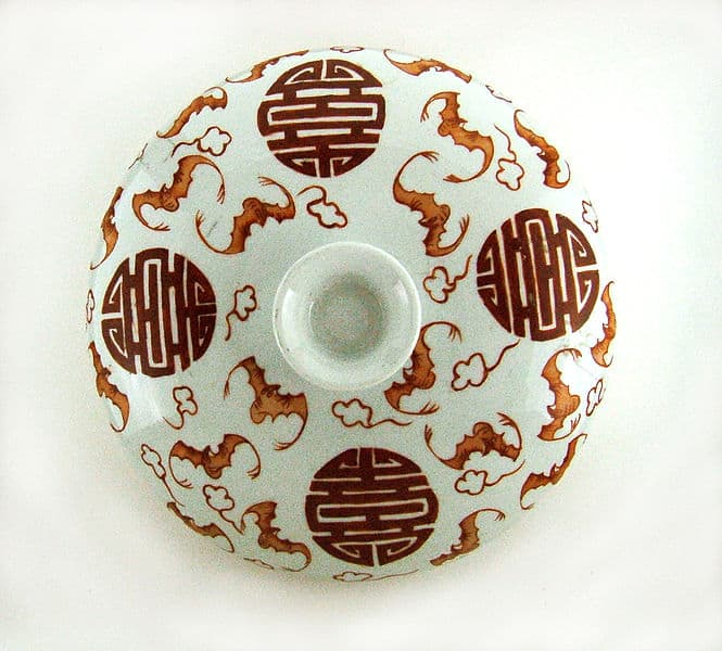 A covered ceramic dish with the Chinese character for longevity (shou) in a sea of flying red bats.