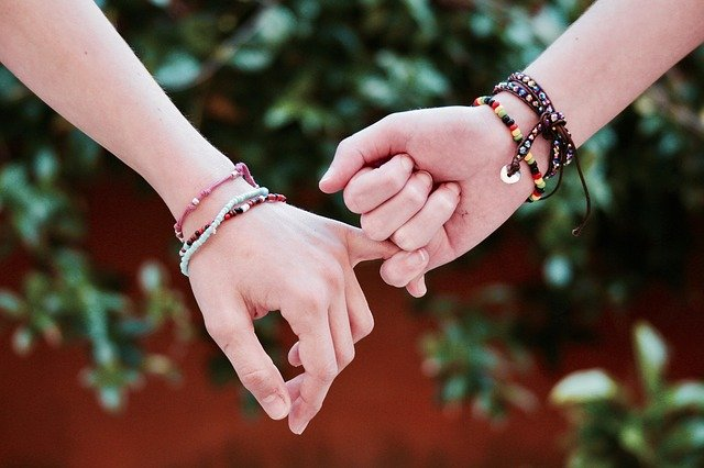 Two friends wearing friendship bracelets holding hands.