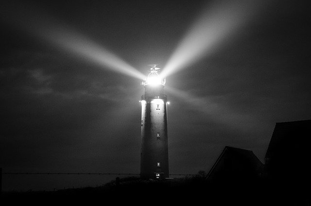 Lighthouse giving off light at night.