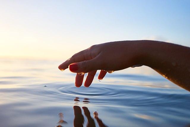 Hand near water.