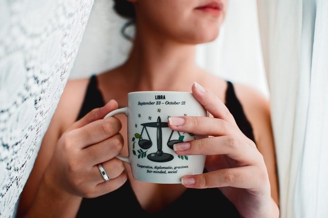 Woman holding mug with libra zodiac sign.