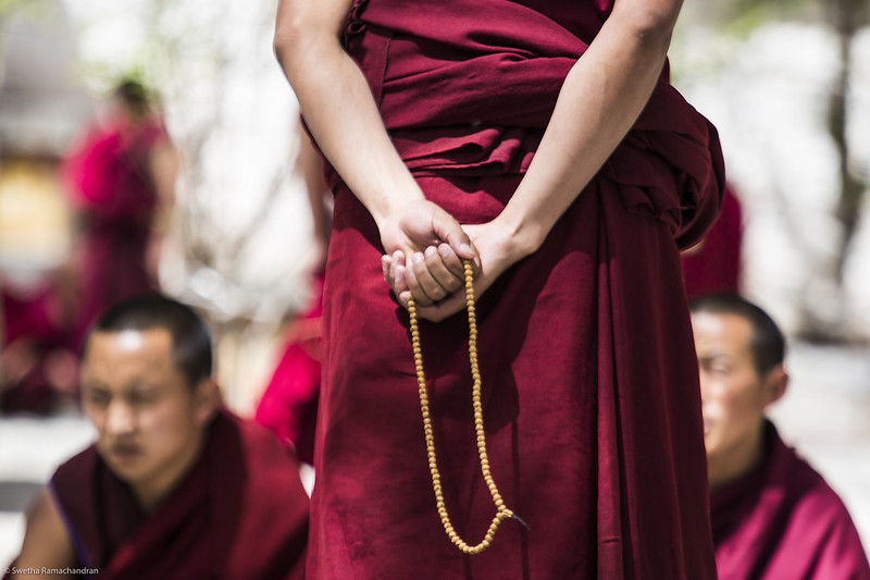 Monk holding prayer beads.