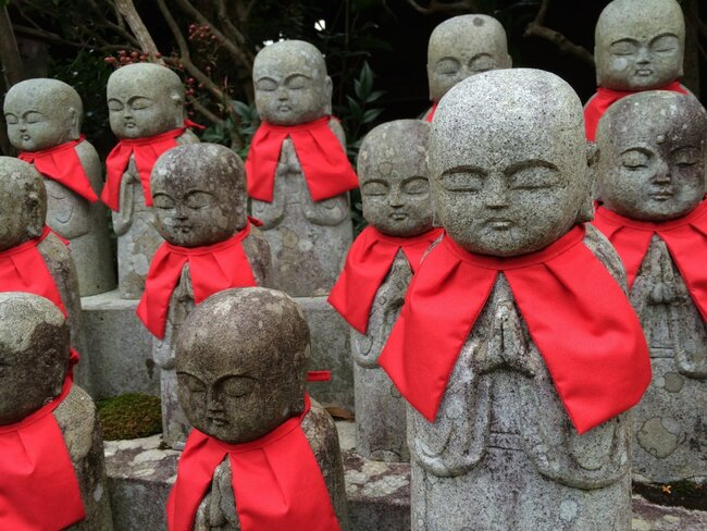 Japanese statues with red bibs.