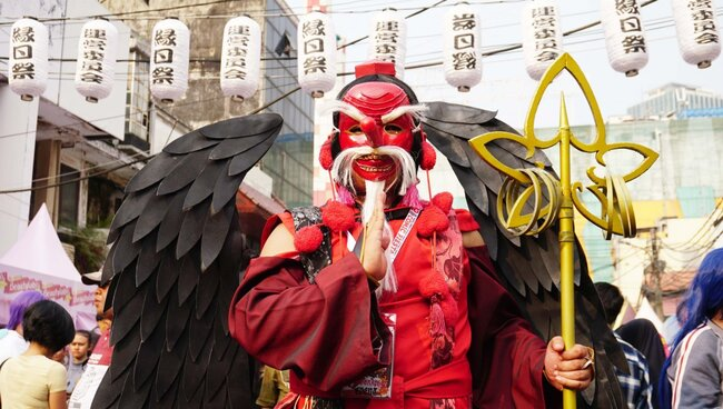 Tengu / A Japanese deity standing at a cosplay event.